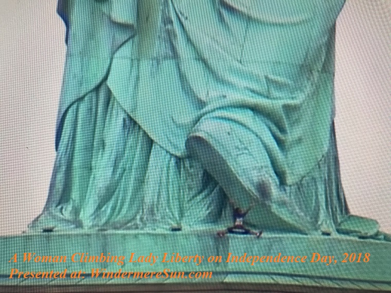 woman climbing Lady Liberty on Independence Day, 2018 final
