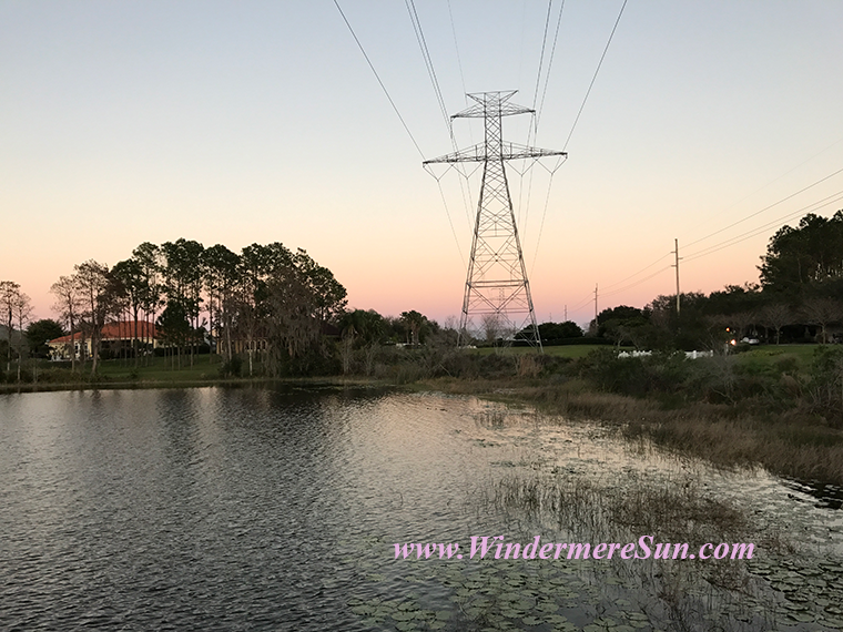 Pink Sunset with powerline tower and water